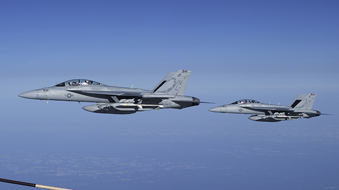 Two U.S. Navy EA-18G Growler electronic warfare jets fly next to a Canadian Forces Airbus CC-150 Polaris tanker over the Mediterranean Sea near Trapani